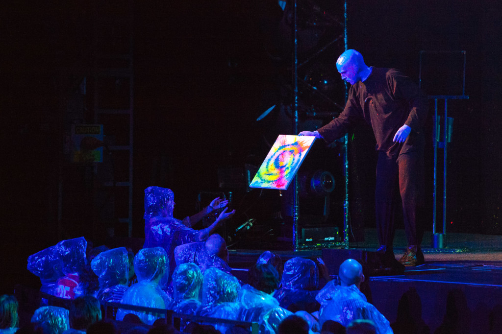One Blue Man hands a freshly made art piece to a little girl. |Cam Peters