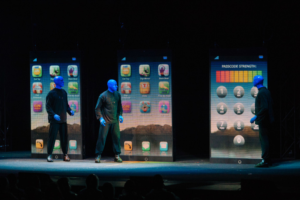 The 3 Blue Men examine large phones on stage. |Cam Peters