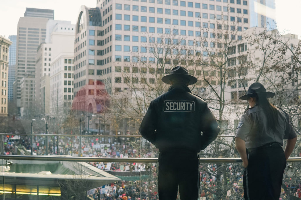Security guards overlook Saturday's crowd from a balcony in Westlake Center.