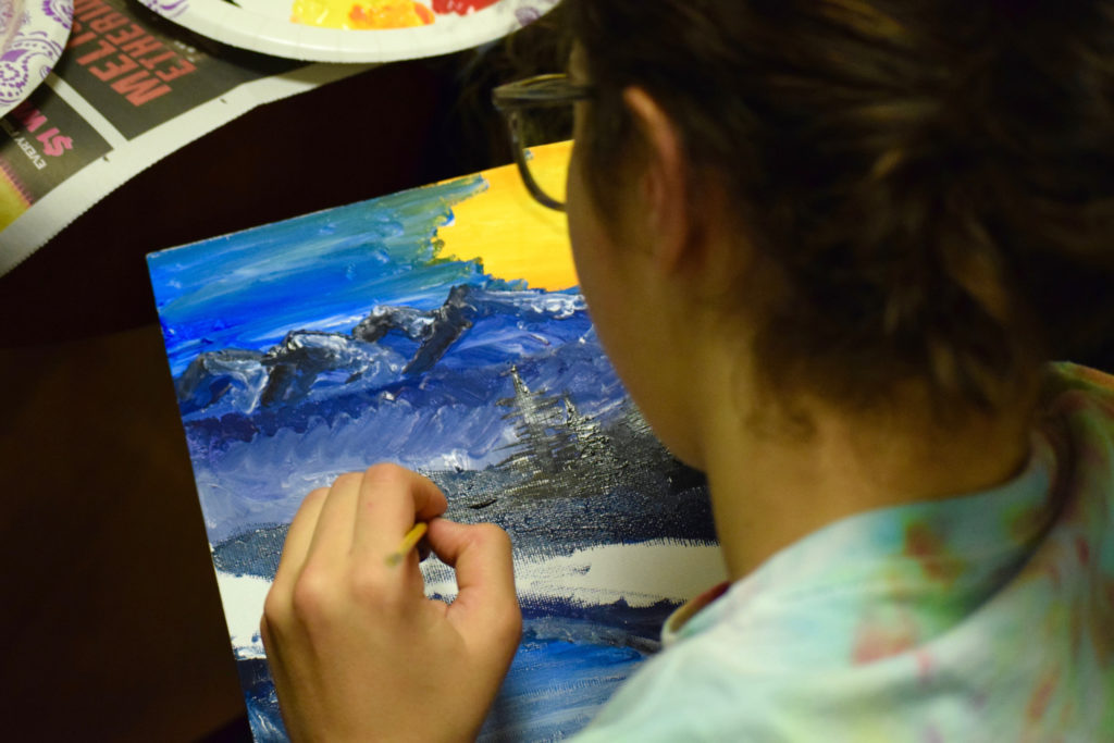 A student carefully follows along to Bob Ross' soothing stroke instructions.